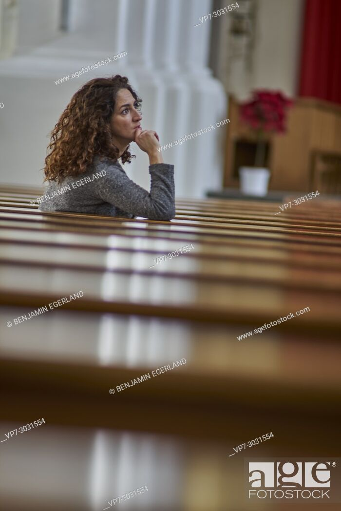 Stock Photo: thoughtful, multi-cultural mature woman sitting in christian church. Half German and half Turkish ethnicity. In Munich, Germany.
