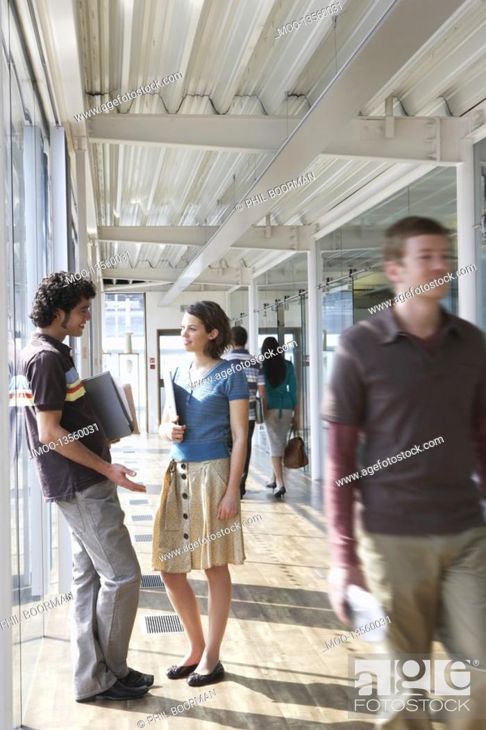 Stock Photo: Office colleagues standing in corridor.
