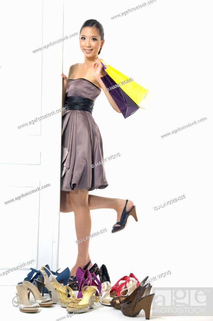 Stock Photo: Woman standing beside a door near a collection of footwear and holding shopping bags.