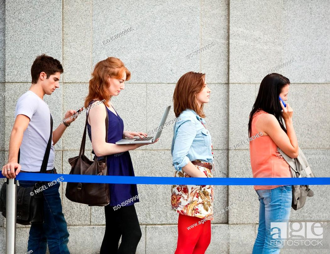 Stock Photo: Four people in a queue, one using a laptop.