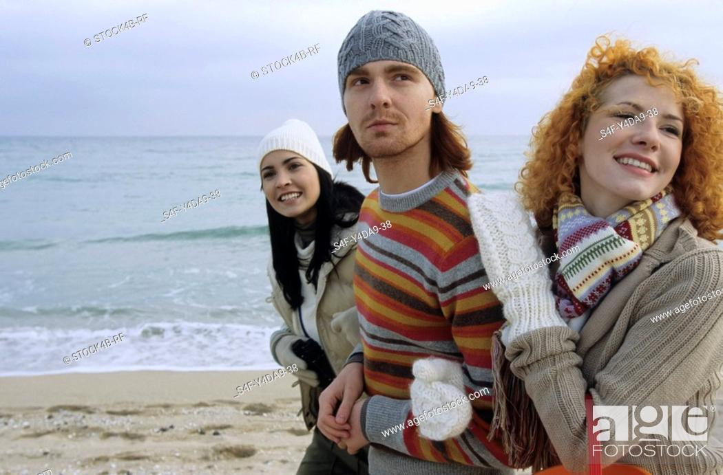 Stock Photo: Three Friends strolling along the Beach Arm in Arm - Fun - Together - Trip.