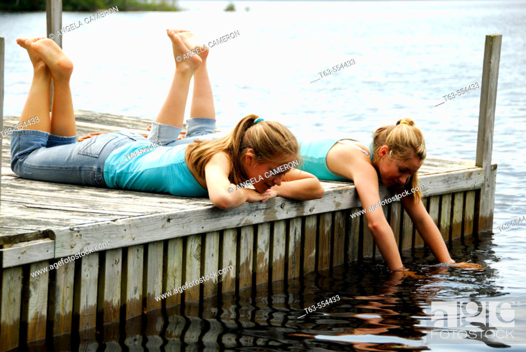 Stock Photo: girl 13, girl 18 laying on dock together.