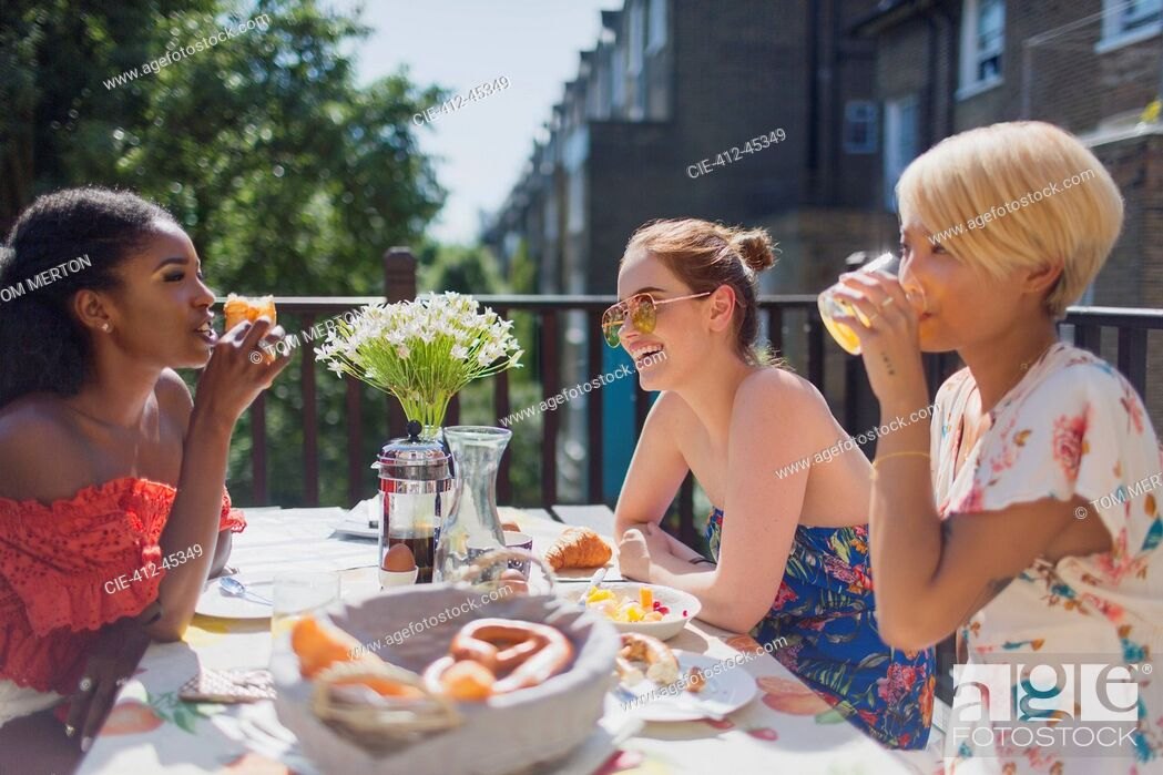 Stock Photo: Young women friends enjoying brunch on sunny apartment balcony.