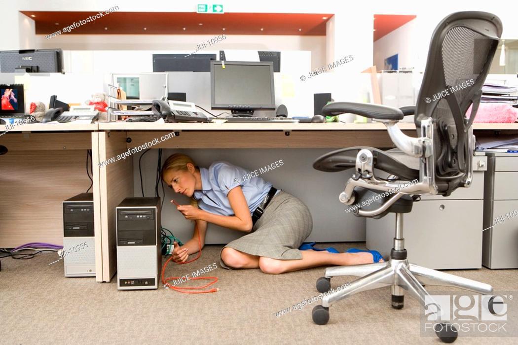 Stock Photo: Businesswoman fixing computer under desk in office.