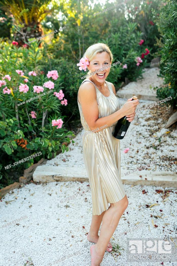 Stock Photo: Happy woman with champagne bottle.