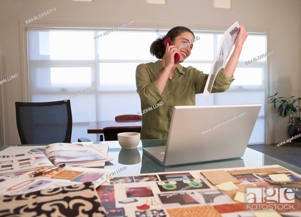 Stock Photo: Mixed Race female designer talking on telephone.