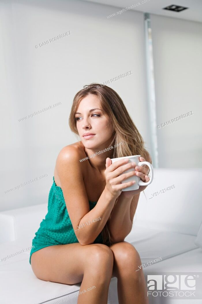 Stock Photo: Blonde spanish woman sitting in a sofa at home with a drink and thinking.
