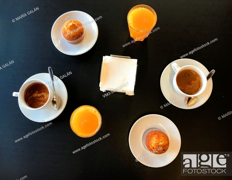 Stock Photo: Breakfast: two cups of coffee, two orange juices and two muffins. View from above.
