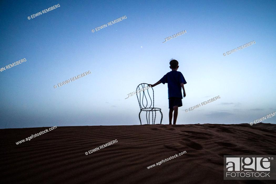 Imagen: Boy with chair in the desert at night, Merzouga, Morocco.