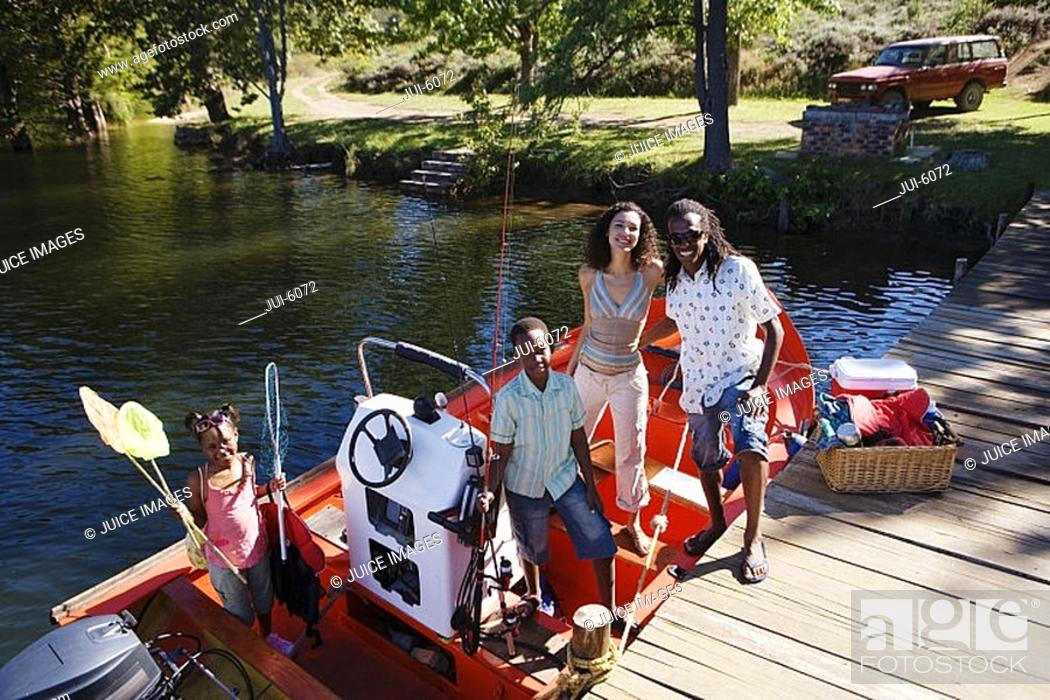 Stock Photo: Family standing in motorboat moored at lake jetty, children 7-10 holding fishing equipment, smiling, portrait.