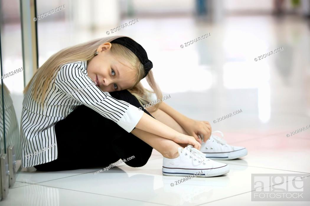 Stock Photo: A tired child in an urban setting. A girl of elementary age sits on the floor of a shop.