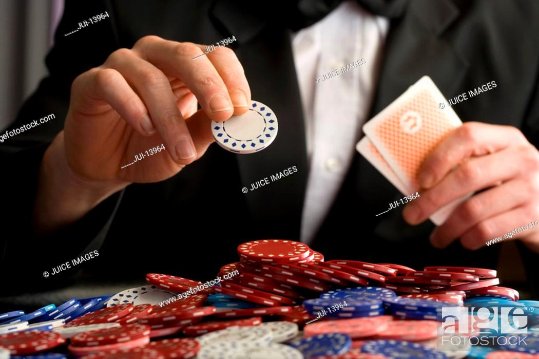 Stock Photo: Man placing gambling chip on pile of chips on table, mid section.