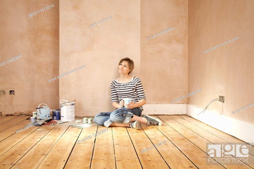 Stock Photo: Woman sitting on floor of unrenovated room holding coffee mug.