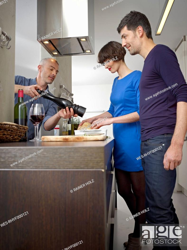 Stock Photo: Germany, Cologne, Men and woman cooking together in kitchen.
