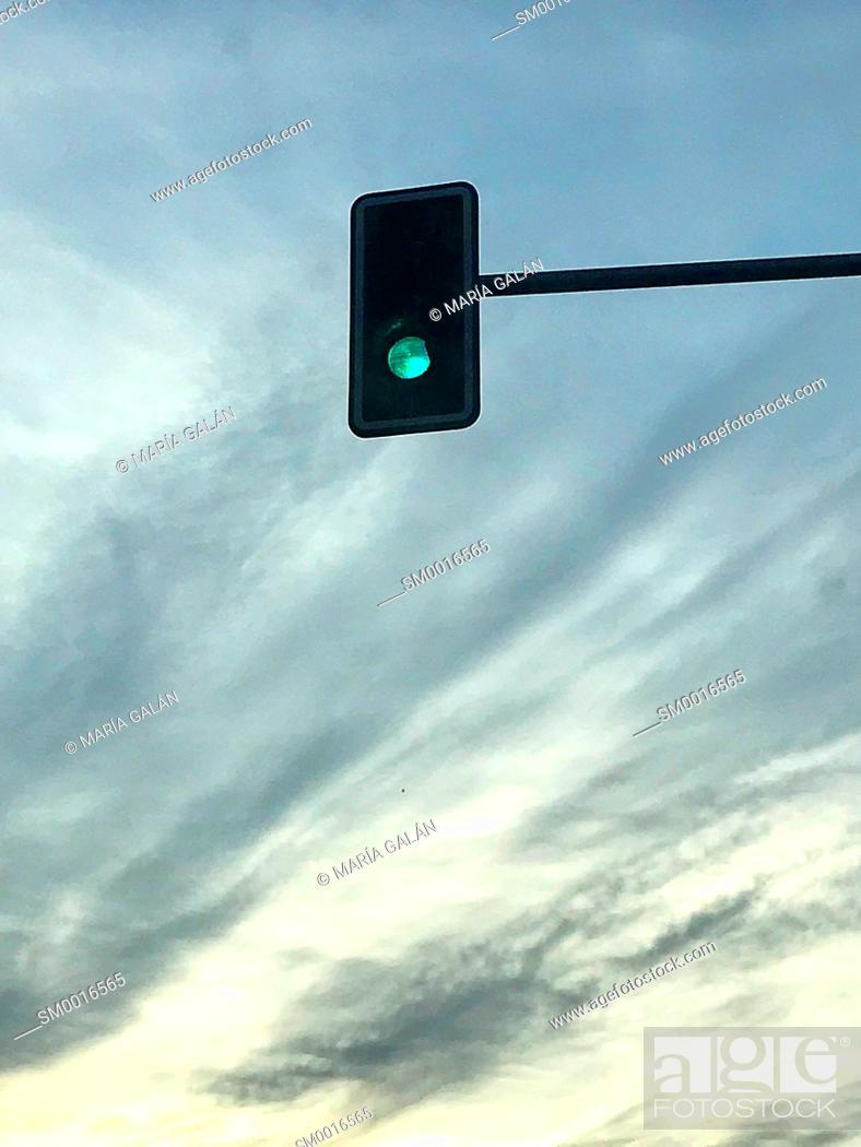 Imagen: Green traffic light against nightfall sky.