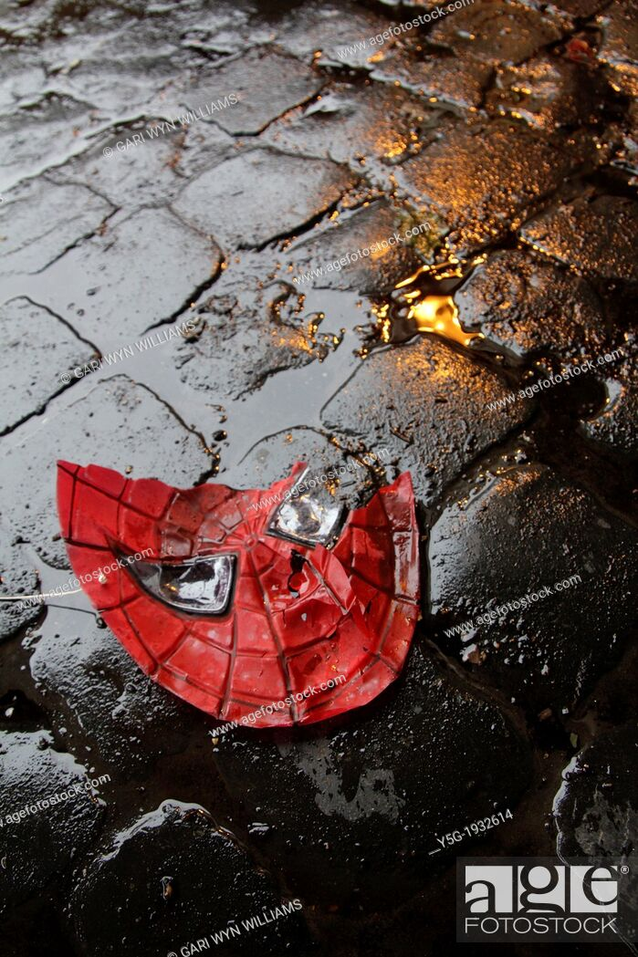 Stock Photo: broken spiderman plastic mask on wet road in city town.