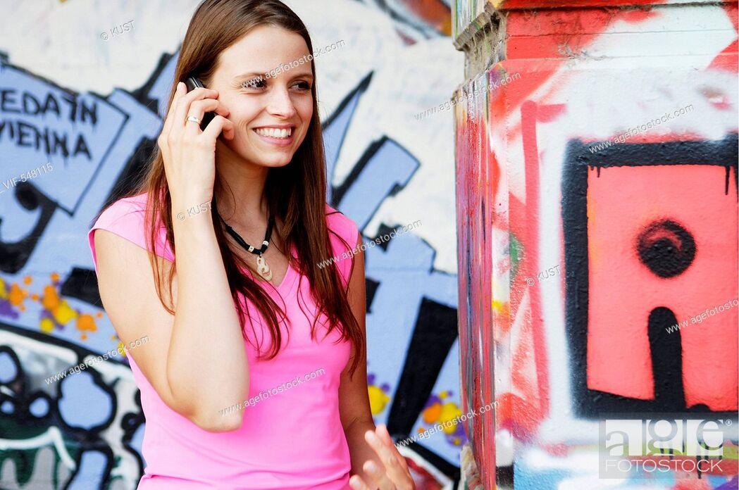 Imagen: junge Frau telefoniert vor Graffitiwand. - Austria, 25/07/2007.