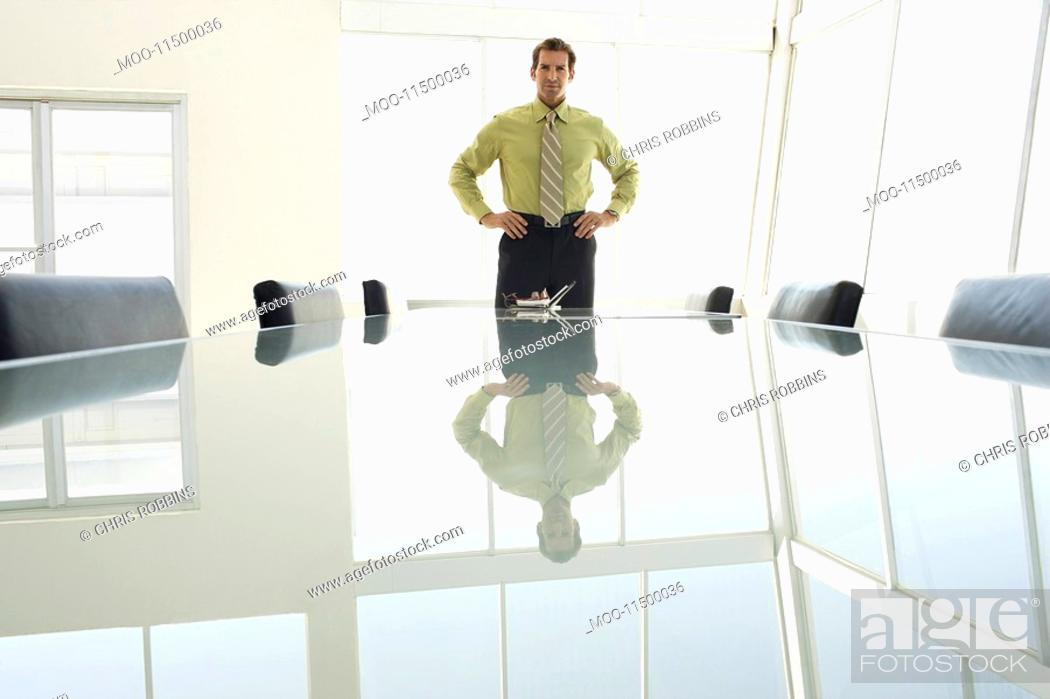 Stock Photo: Businessman with hands on hips at conference table portrait.