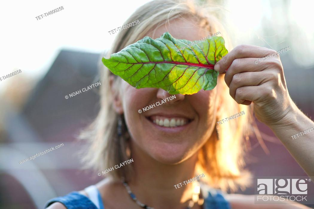 Stock Photo: Smiling woman holding leaf in front of her face.