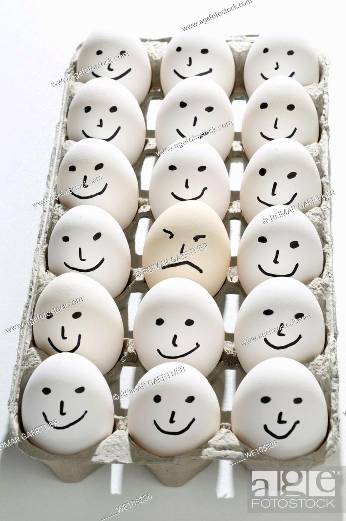 Stock Photo: Package of bright backlit eggs with smiling faces except for one grumpy sad face.