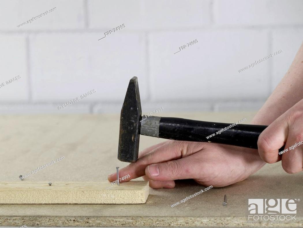 Stock Photo: Hammering a nail.