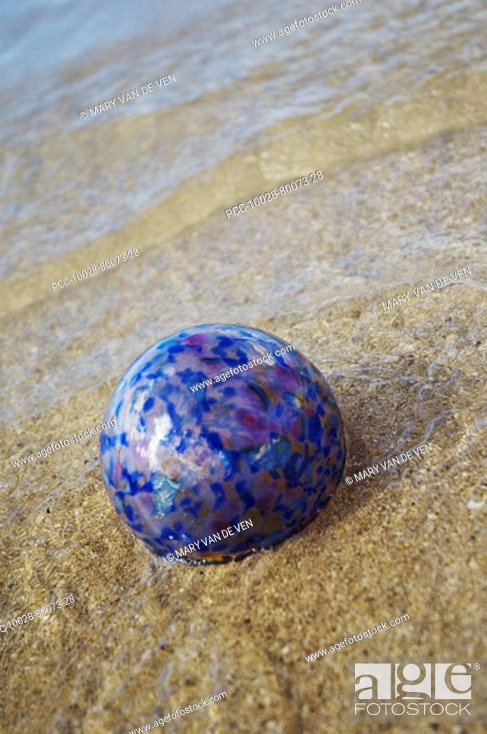 Stock Photo: Art glass gloat in shallow ocean water on sandy beach.