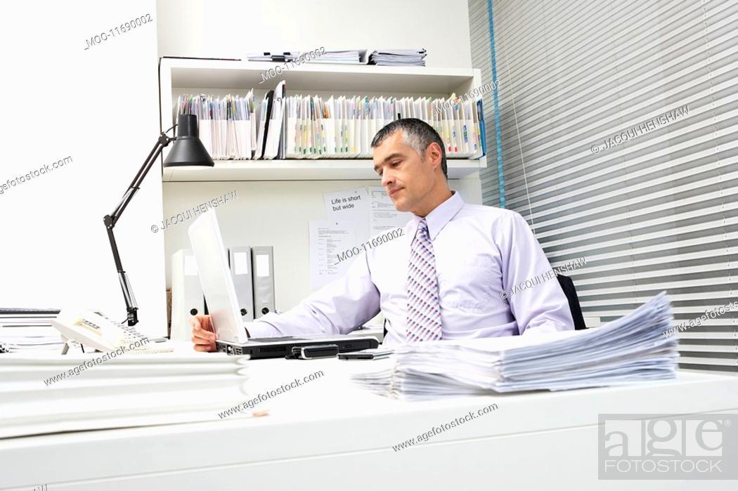 Stock Photo: Businessman using laptop at office desk.