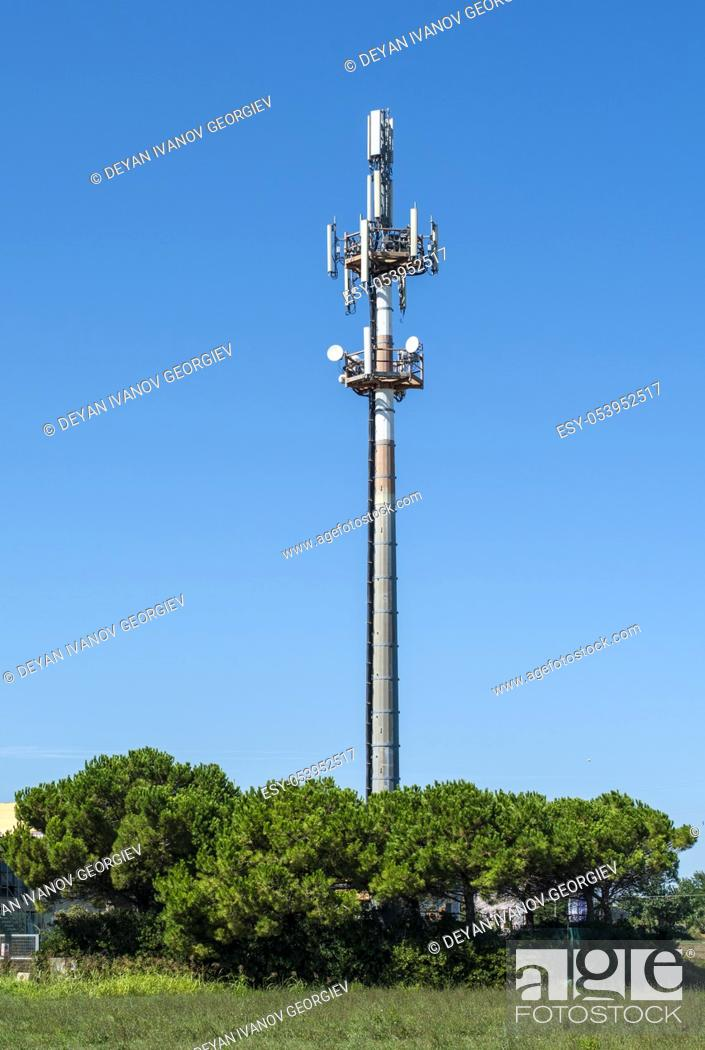 Stock Photo: 5G antenna outside the city. GSM Antenna in the nature. New 5G technology for internet concept. New Transmitter tower and trees.
