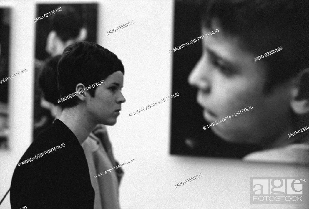 Stock Photo: A young woman visiting the biennial fair dedicated to photography. Cologno Monzese, 1966.