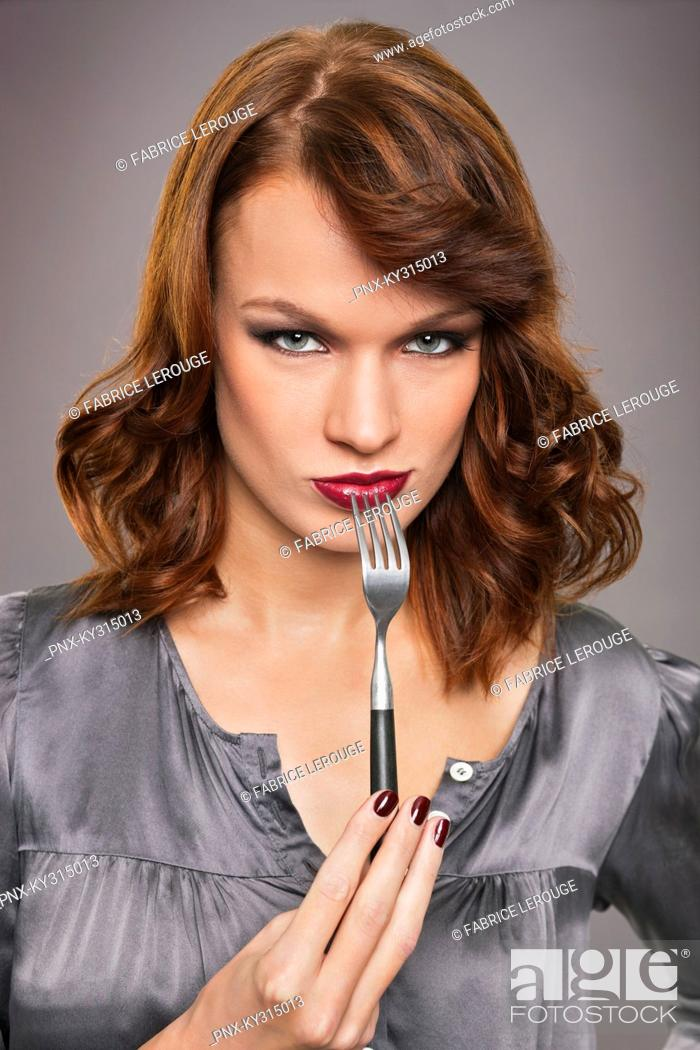 Stock Photo: Young woman holding fork.