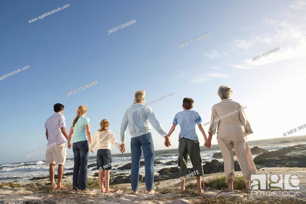Stock Photo: Three generation family holding hands on seashore back view.