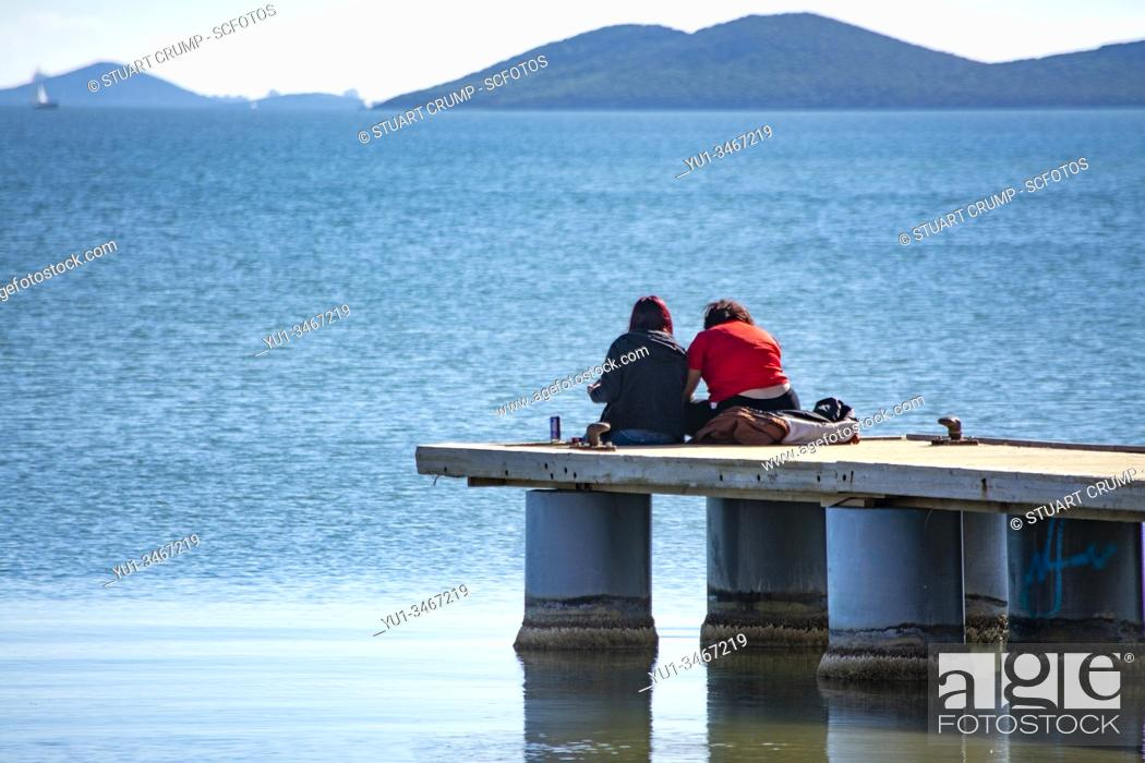 Stock Photo: Couple sitting on the end of the jetty at Los Alcazares in Murcia Spain.