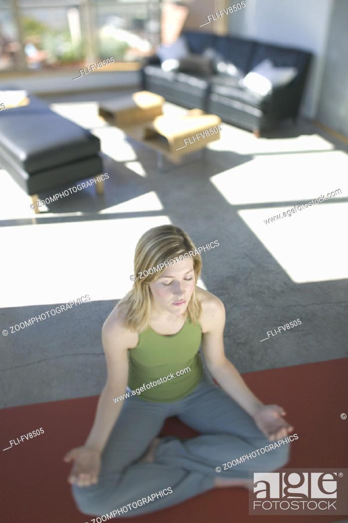 Stock Photo: Woman Meditating in Loft Vancouver British Columbia.