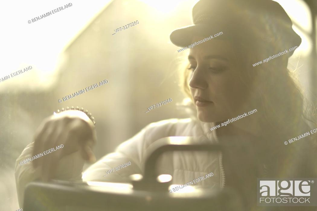 Stock Photo: young sensitive woman sitting in public transport, in city Cottbus, Brandenburg, Germany.