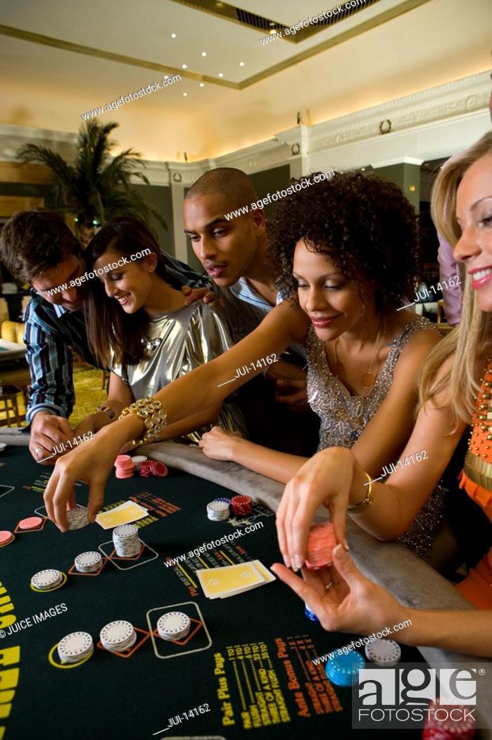Stock Photo: Young men and women gambling in casino, side view.
