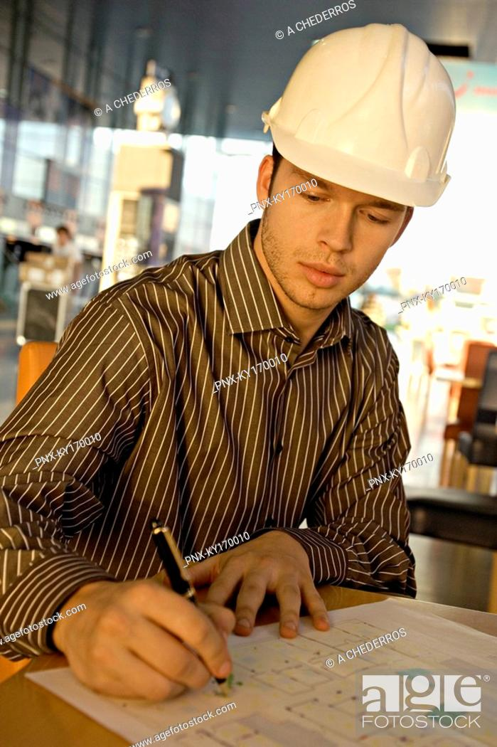 Stock Photo: Male architect working on a blueprint.