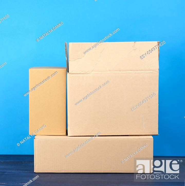 Stock Photo: stack of cardboard boxes of brown kraft paper on a blue wooden table, moving concept.
