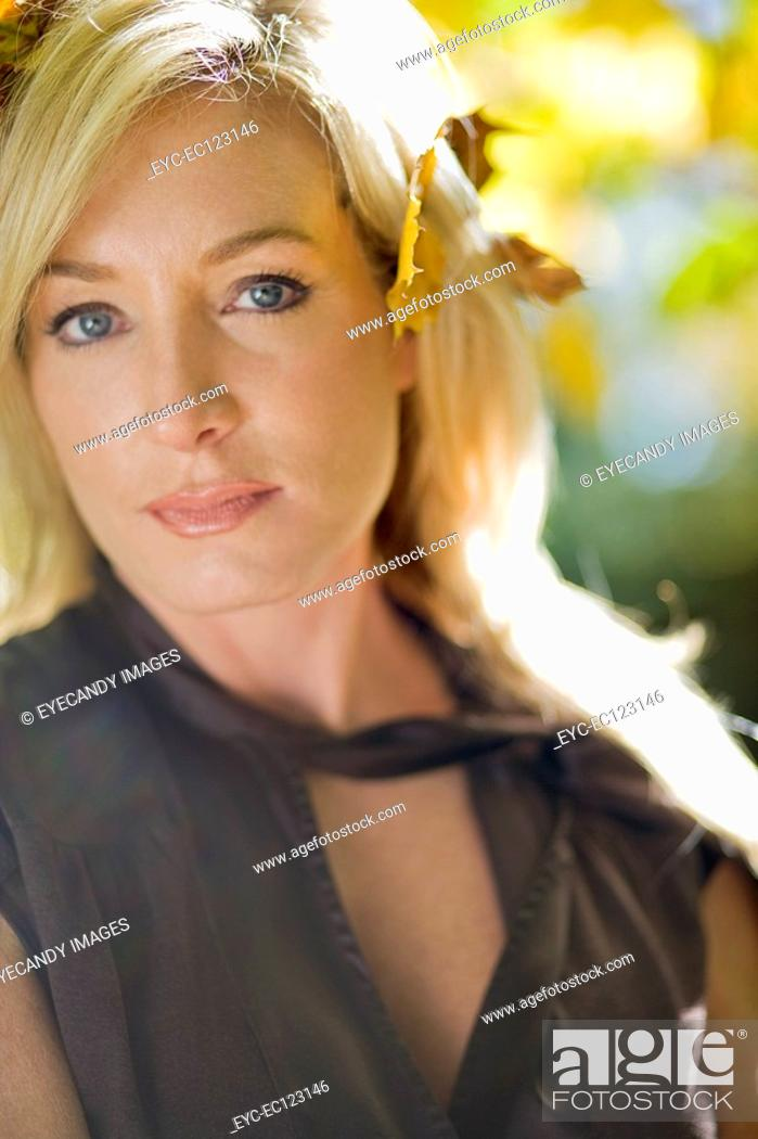 Stock Photo: Close-up of serious blonde woman with leaves in hair.