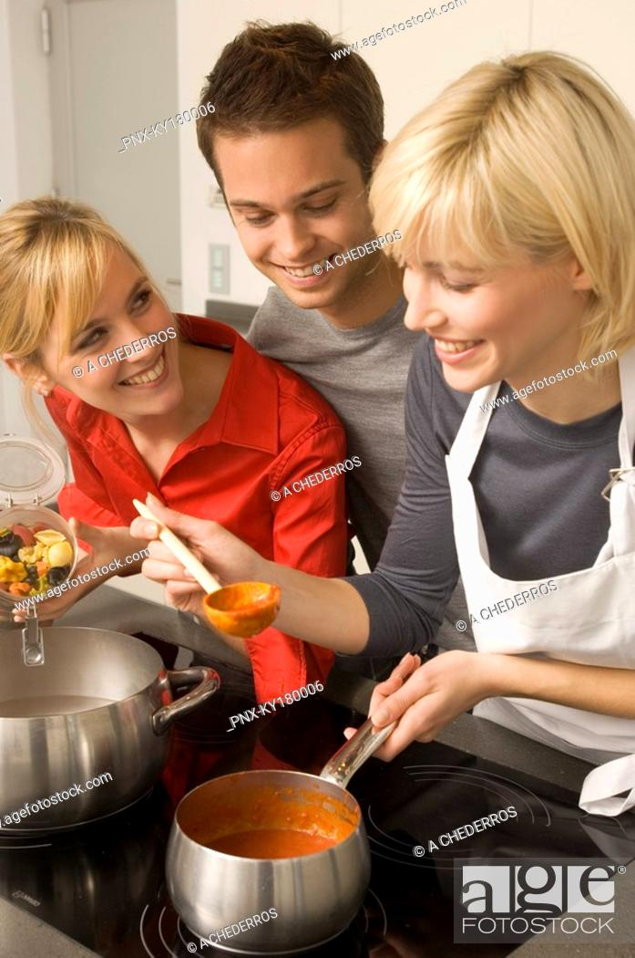 Stock Photo: Two young women and a young man preparing food in the kitchen.