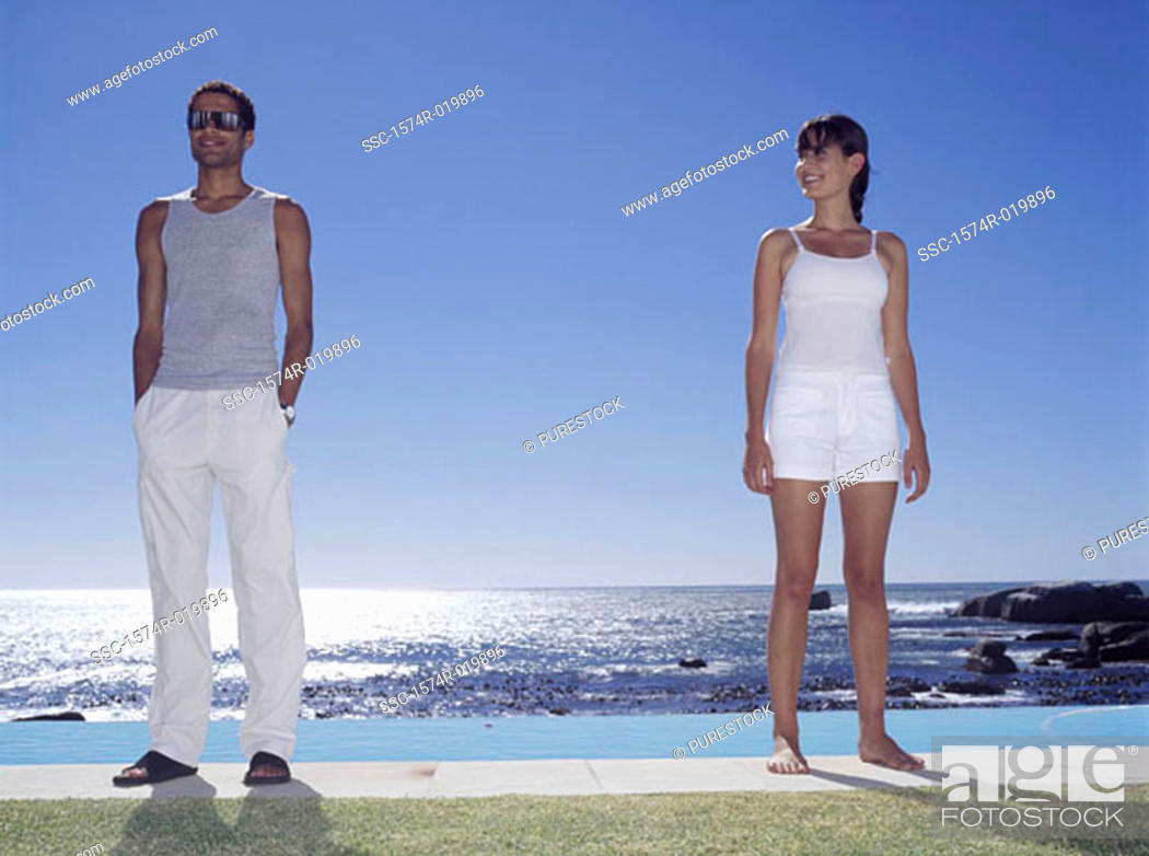 Stock Photo: Young couple standing at the poolside.