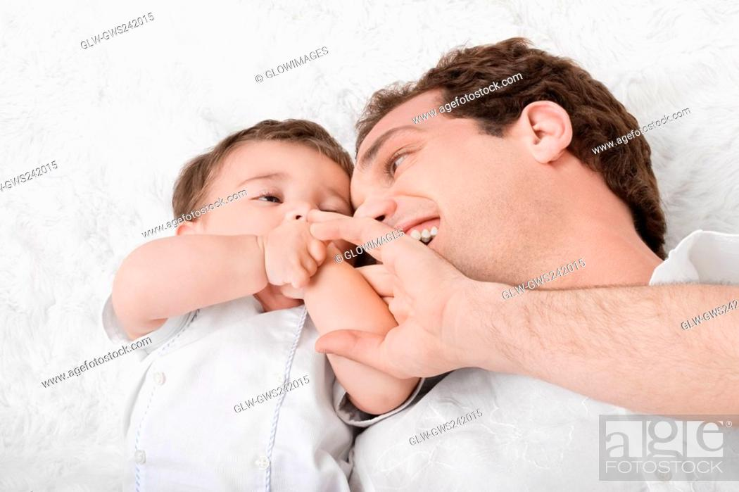 Stock Photo: Close-up of a young man lying with his son.
