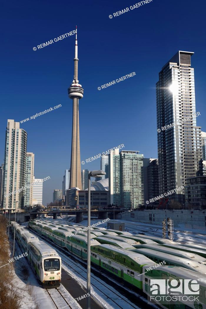 Stock Photo: GO trains in downtown Toronto waiting for rush hour with CN tower, Rogers Centre stadium and highrise condominiums.