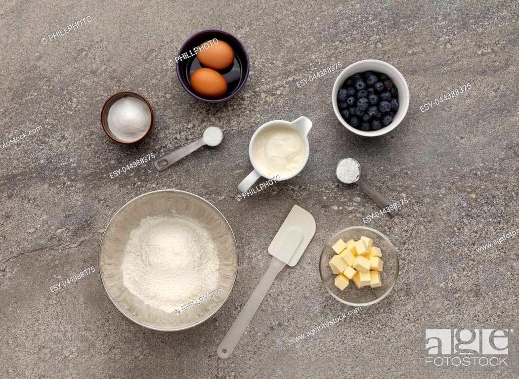 Stock Photo: Blueberry muffin ingredient mixture, shot on a stone work surface, inluding eggs, flour, butter and sugar.
