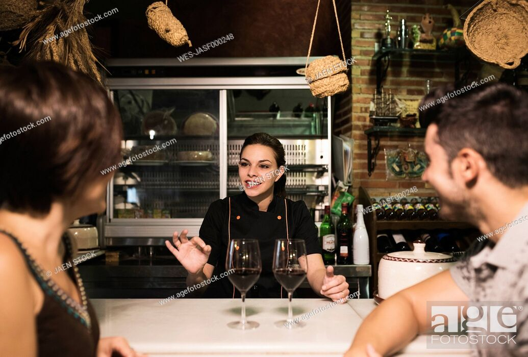 Stock Photo: Waitress talking to couple at bar with red wine glasses.