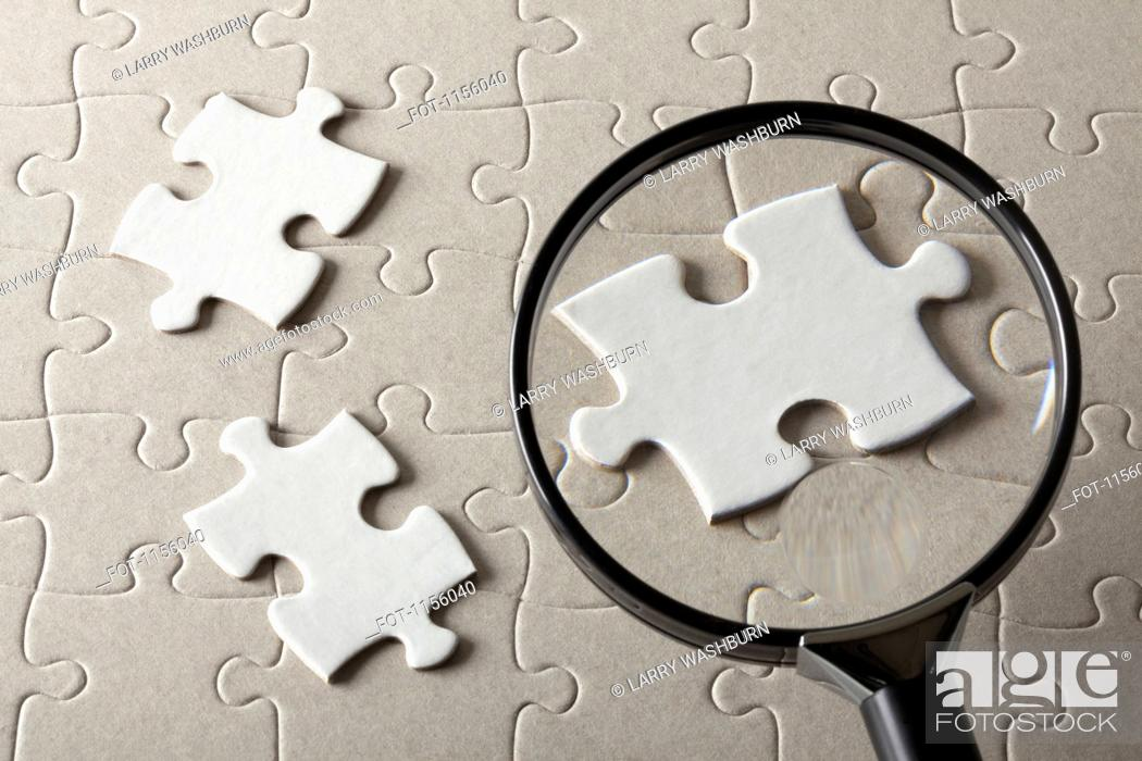 Stock Photo: Puzzle pieces on a jigsaw puzzle being magnified by a magnifying glass.