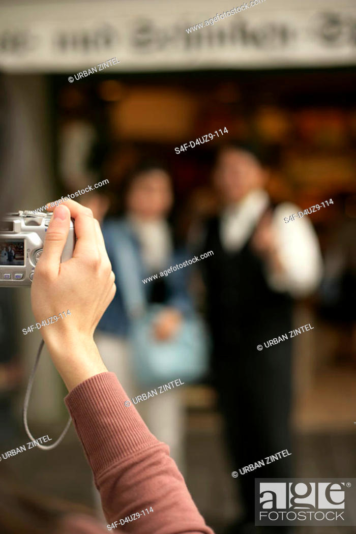 Stock Photo: Woman taking a picture of two people in front of a shop, selective focus.