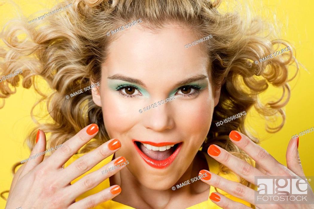 Stock Photo: Young blonde woman against yellow background.