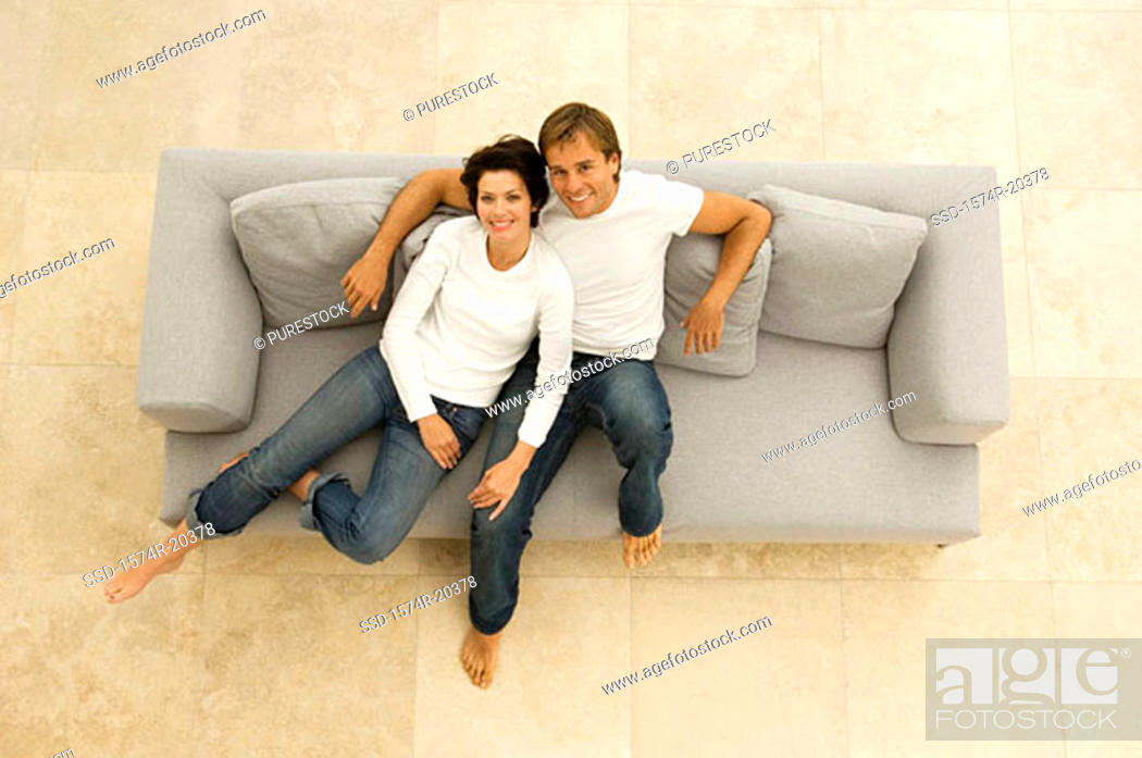 Stock Photo: Portrait of a young couple sitting on a couch and smiling.