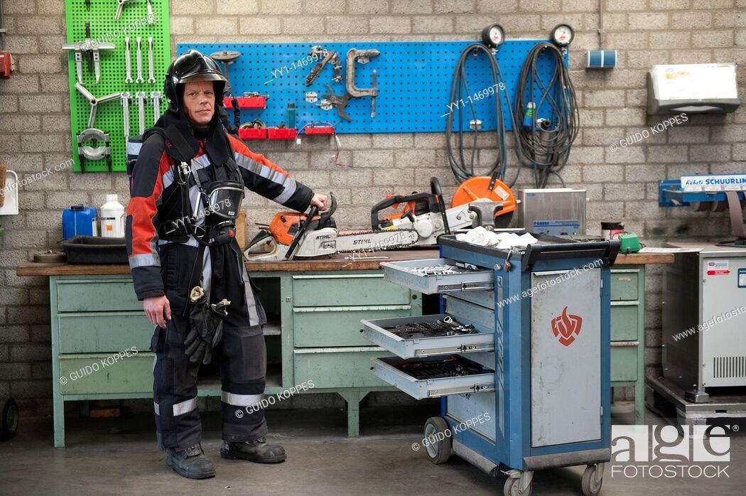 Stock Photo: Tilburg, Netherlands. Firefighter in fireproof turnout gear on his regular job inside the barracks.