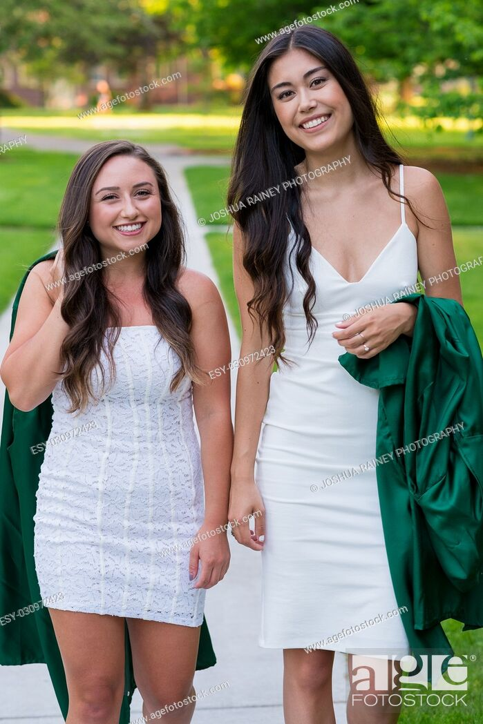 Stock Photo: Two college girls and best friends walk on a sidewalk while holding their caps and gowns before graduation on a university campus during the Spring in Oregon.